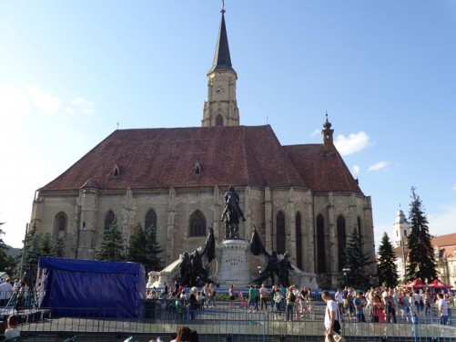 Union Square (Piata Unirii) busy with people. Union Square is the largest square in Cluj situated in the city centre. In the background is St Michael's Church, which was built in the late 14th century in Gothic style and named after the Archangel Michael, the patron saint of Cluj-Napoca.
