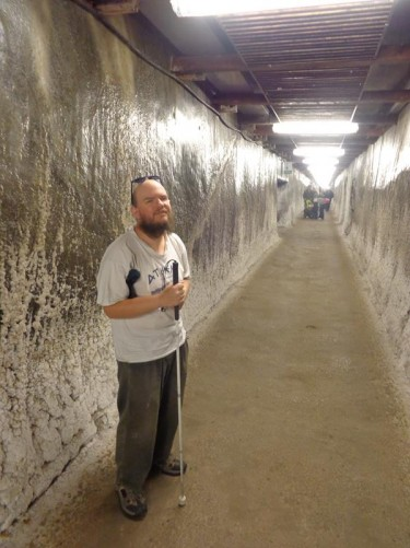 Tony standing in a long straight access tunnel heading into the mine.