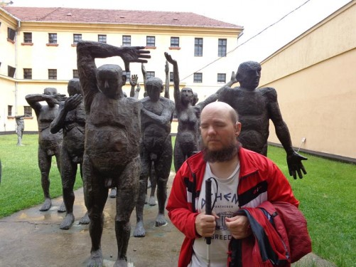 Tony in front of statues of people being tortured in a garden behind the prison, part of an exhibition.