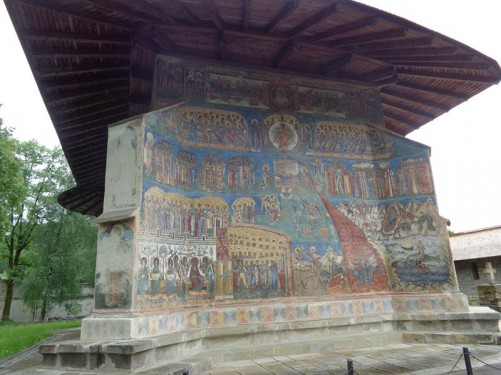 Now at Voroneț Monastery. View of a side wall of the Church of St George completely covered with frescos. These feature an intense shade of blue, known in Romania as Voroneț blue, which can be seen in this picture. The monastery is located in Voroneţ village, now part of Gura Humorului town. The monastery was constructed by Stephen the Great in 1488 to commemorate victory at the Battle of Vaslui.