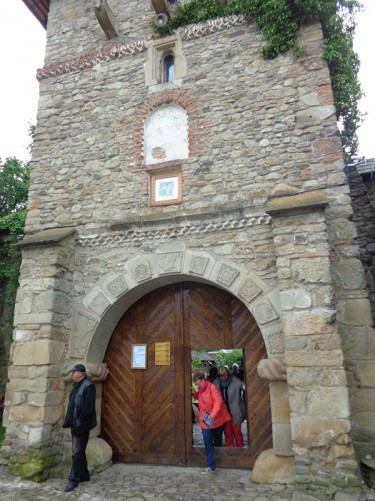 Outside the entrance gate. A large wooden doorway leading through the square shaped stone tower in the monastery walls.