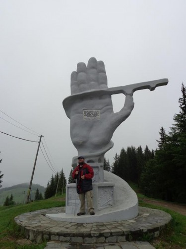 Tony in front of a giant stone hand in the mountains of Suceava County. It was built to commemorate the joining of two roads through the mountains. It was chilly when Tony was up there, about 7 degrees Celsius.