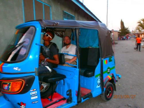 Now parked with Tony still sitting in the back of the vehicle and the driver in front. It is a compact three-wheeled vehicle known as a Bajaj (the name of the Indian manufacturer).