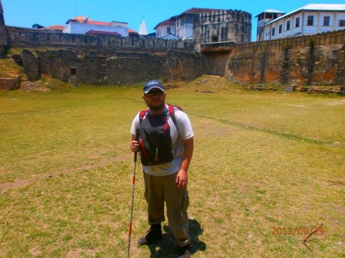 Again Tony within the Old Fort. Stone walls around the perimeter with a round tower visible in one corner behind.