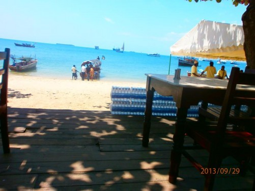 Afternoon. View from a café terrace to a sandy beach. Traditional dhows (wooden sailing boats) in the sea.