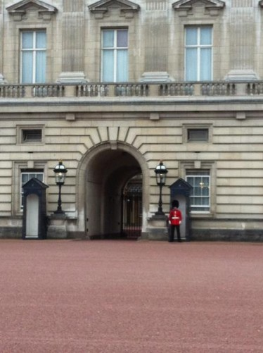 The front of Buckingham Palace. Across the courtyard a ceremonial guard is standing in front of a sentry box. He is wearing the distinctive Queen's Guard uniform including red tunic and bearskin hat.