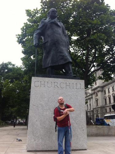 Tony in front of a bronze statue of Winston Churchill in Parliament Square. The statue was unveiled in 1973. It is 3.7 metres (12 feet) high and stands on a 2.4 metres (8 feet) high stone plinth.