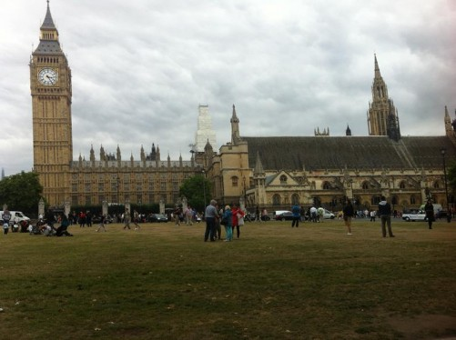 People walking and sitting on the grass in Parliament Square. The Palace of Westminster in the background with a good view of Big Ben (Elizabeth Tower).