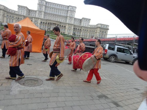 Looking towards the front of the massive Parliament Palace. In the foreground, a parade featuring men in colourful traditional dress and carrying drums and other percussion instruments.