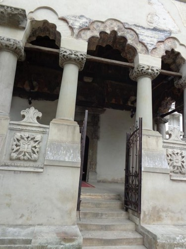Closer view of the front entrance to Coltea Church. Short stone columns supporting arches. Faded painted decoration around the arches. A few steps leading up to an entrance porch.