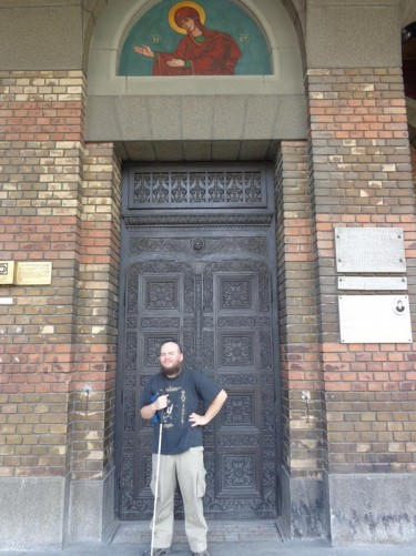 Tony outside a doorway into the Orthodox Metropolitan Cathedral. The cathedral is the seat of the Archbishop of Timișoara and Metropolis of Banat. It was built between 1936 and 1941. It has 11 towers, with the highest central one standing at 90.5 metres (297 feet) in height.