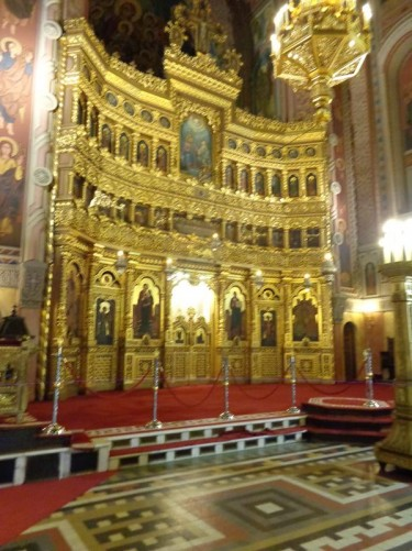 At the tall main altar decorated in gold with painted panels in niches.