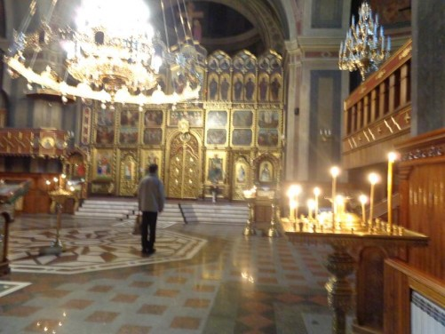 Inside the Holy Spirit Orthodox Cathedral looking towards the golden main altar. Candles on a stand immediately in front.
