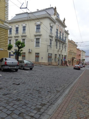 Looking from cobbled Ivan Franko Street into Tsentralna Square. The building in front is Chernivtsi Art Museum, which was established in 1988. The building dates from 1901 and was designed by Hubert Gessner as the head office of Bukowiner Sparkasse bank. It is regarded as an outstanding example of Vienna Secession architecture. The front façade features a large mosaic depicting twelve ancient gods symbolising the twelve crowned provinces of the Austro-Hungarian Empire. A pair of stone statues stand on the roof.