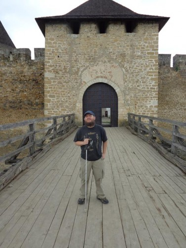 Tony on a wooden bridge crossing over a moat to the fort's stone entrance tower and gate.