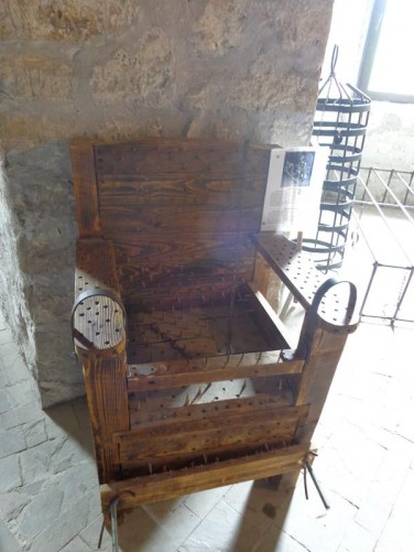 Inside the fortress in a room displaying torture equipment. In front a large wooden chair covered with vicious metal spikes.