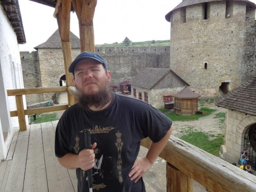 On a wooden balcony looking into the inner courtyard. Behind Tony is the rectangular entrance tower with the tall crenellated outer wall running on either side. A large round tower stands in one corner.