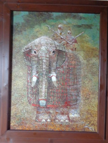 A painting of an elephant in armour with two soldiers also in armour on top. Elephants were used by the Ottoman army to attack the fortress in the Middle Ages.