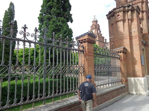 Tony walking outside the university's perimeter wall. The prominent red-brick clock tower of the former Monastery building can be seen opposite.