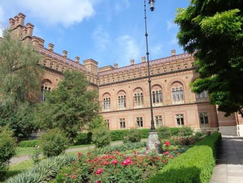 Inside the Chernivtsi National University grounds. An impressive red-brick building in front.