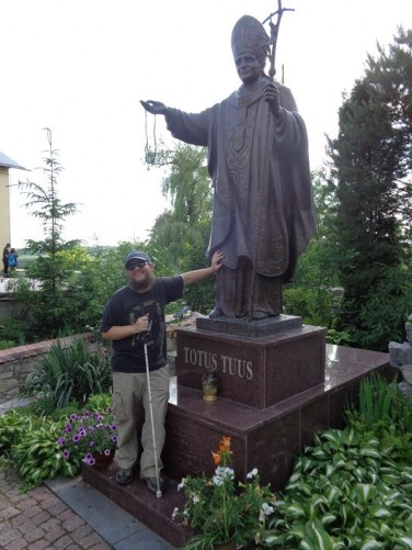 Tony touching a statue of Pope John Paul II in the garden of the Cathedral of Saints Peter and Paul. The statue was unveiled in June 2007.