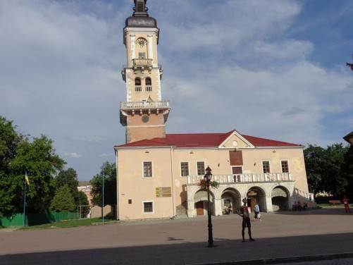 Outside the Town Hall: a two storey building painted pink with a tall clock tower at one end.