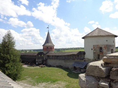 Still up on the walls with two more towers in view. The one on the left is Tenchynska Tower, which dates from the 14th to 16th centuries. Covered wooden walkways run along the walls in both directions from the tower. On the right is the White Tower (also known as Laska Tower) constructed in the 15th century. This large white-painted tower housed an artillery arsenal.