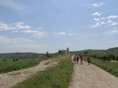 A track passing along a ridge across the grassy landscape. A bell tower standing at the far end.
