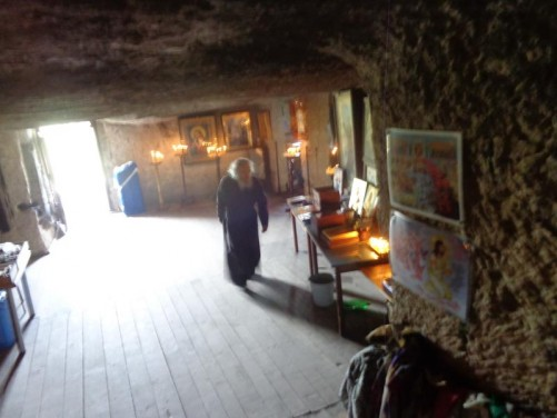 A monk inside the monastery. Religious souvenirs for sale.