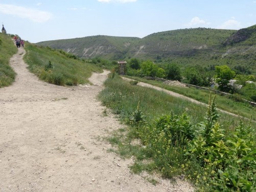 Paths leading through grass and flowers at Old Orhei. Cliffs visible at the far side of the Răut River.