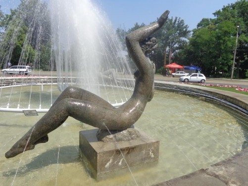 A large round fountain with stylised sculptures of female nudes sprayed with jets of water.