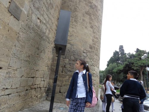 People, mostly school children, standing outside a gate leading into Baku's Old City.