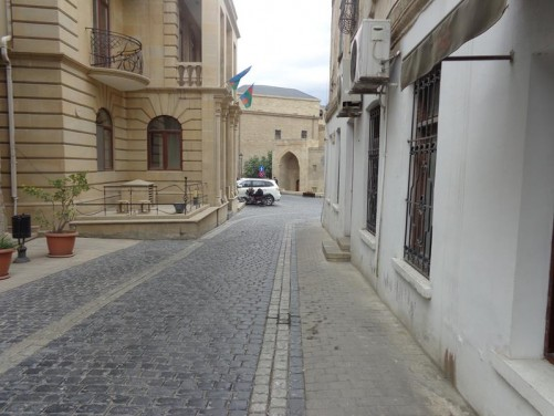 A cobbled street. To the left side, possibly a government building, with a pair of Azerbaijani flags flying above the entrance.