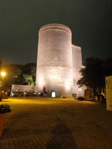 Maiden Tower (Guz Qalasi) lit up in the darkness. This mysterious and eccentric tower was built somewhere between the 7th and 12th centuries and may have served as a fire beacon, defensive fortification, astronomical observatory, or Zoroastrian temple.