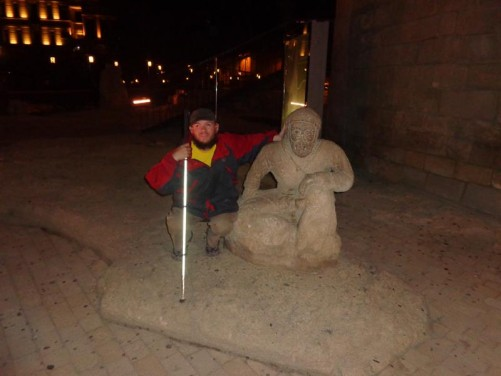 Old stone statue of a man sitting in a crouched position. Tony crouched along side. Taken at the foot of Maiden Tower.