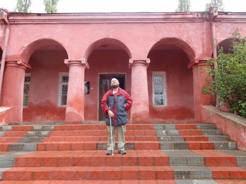 Tony outside a single storey red-painted building again within Sheki fortress.