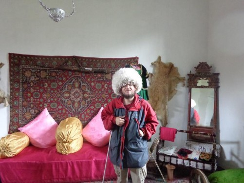 A traditionally decorated bedroom inside the Museum of Applied Art. Tony wearing a large, fluffy, silly-looking wool hat.