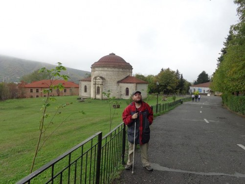 Tony standing on a road within Sheki fortress. The Albanian Church and other buildings in the background.