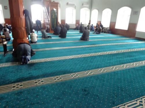 Inside the mosque. Men kneeling in prayer.