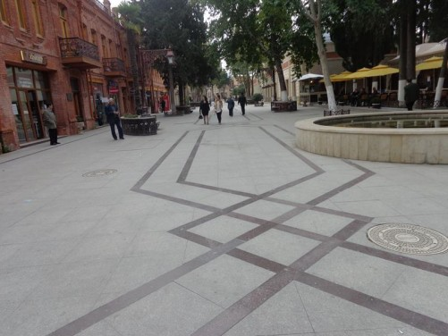 Javad Khan Street: A wide leafy pedestrian shopping street lined with historic buildings.