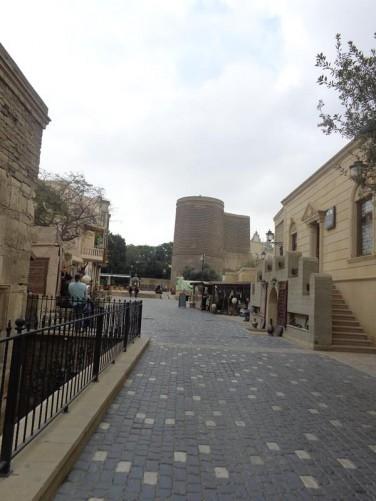 Looking along a pedestrian street containing a few shops. Maiden Tower (Guz Qalasi) at the far end.