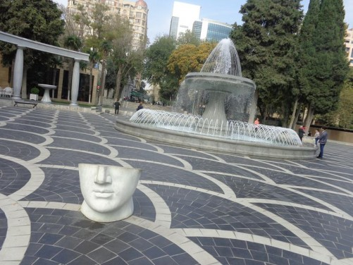 Half a stone head – a public art work in Fountain Square. The head is horizontally cut into two, with only the lower part up to the top of the nose present.