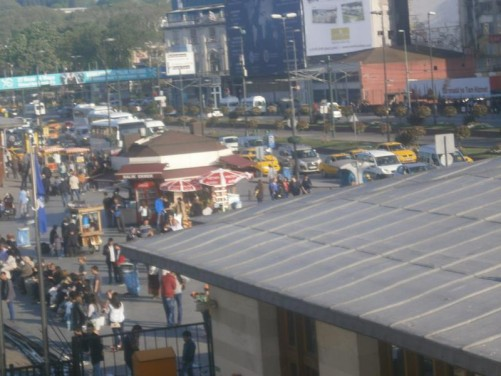 View of activity near to local sea-bus terminals. People standing waiting to board boats. Kiosks and stalls selling food and other supplies. Queues of cars on the road behind.