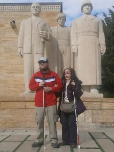 Tatiana and Tony in front of three stylised male statues. The statue on the right is a soldier, in the middle a peasant in village clothing and to the left a youth and intellectual holding a book.