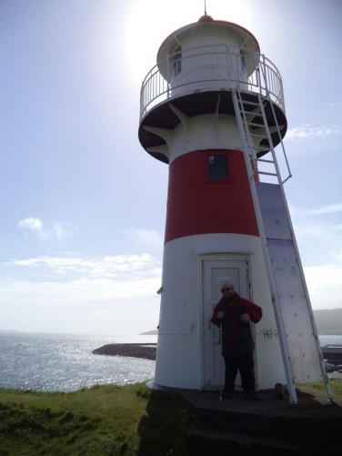 View of the lighthouse and the sea below. Tony standing in the lighthouse's doorway.