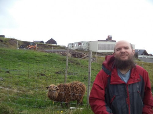 Tony in the foreground with a shaggy long-haired sheep behind. A single storey stone building beyond.