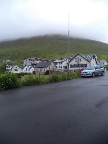 A road heading uphill on the edge of Fuglafjørður. Beyond a mountain disappearing up into the cloud.