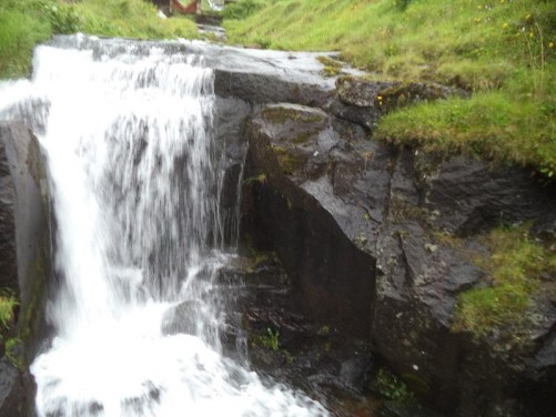 A stream with water flowing over a small waterfall. Still in Fuglafjørður.