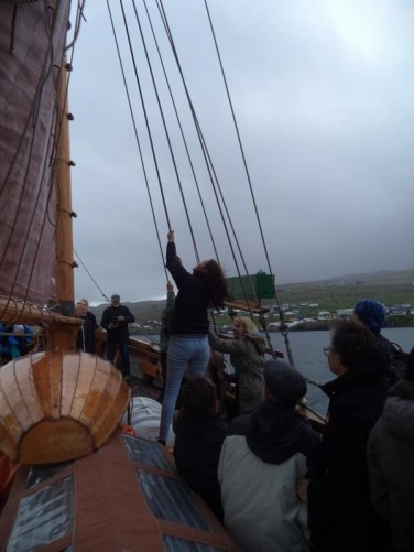 A woman rising a sail on one of the boat's three masts.