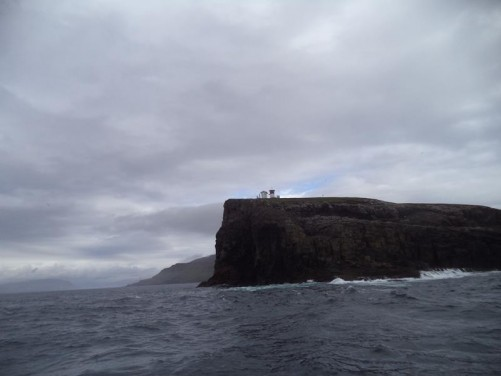 A lighthouse standing on top of a high rocky headland on Nólsoy island.